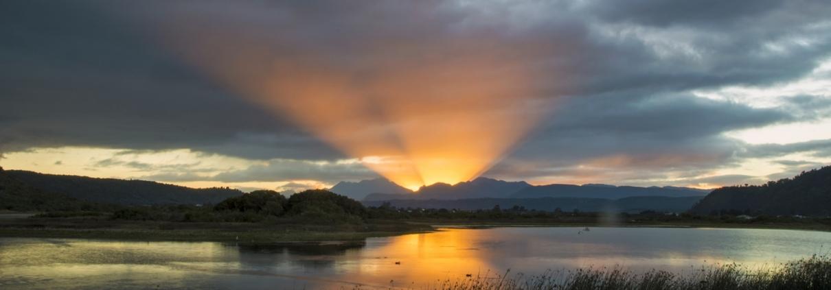 Sun bursting over mountains Swartvlei Sedgefield